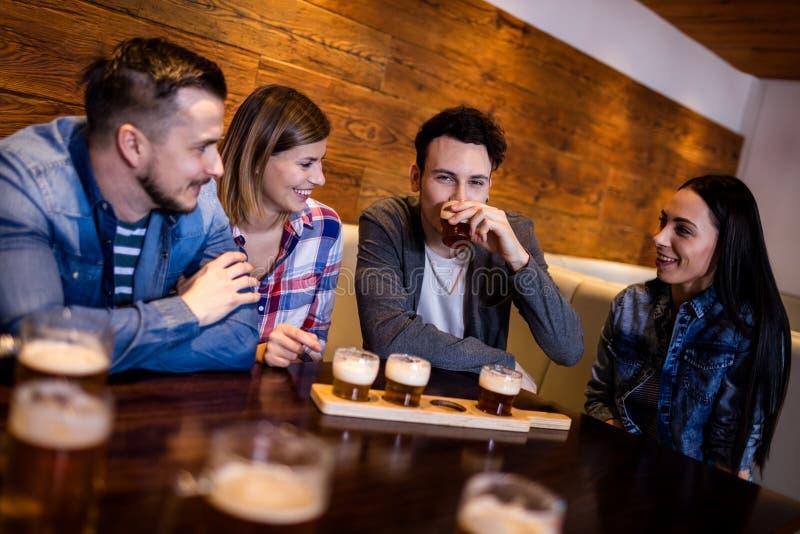 Freunde, die Bier bei Tisch im Restaurant essen lizenzfreie stockbilder