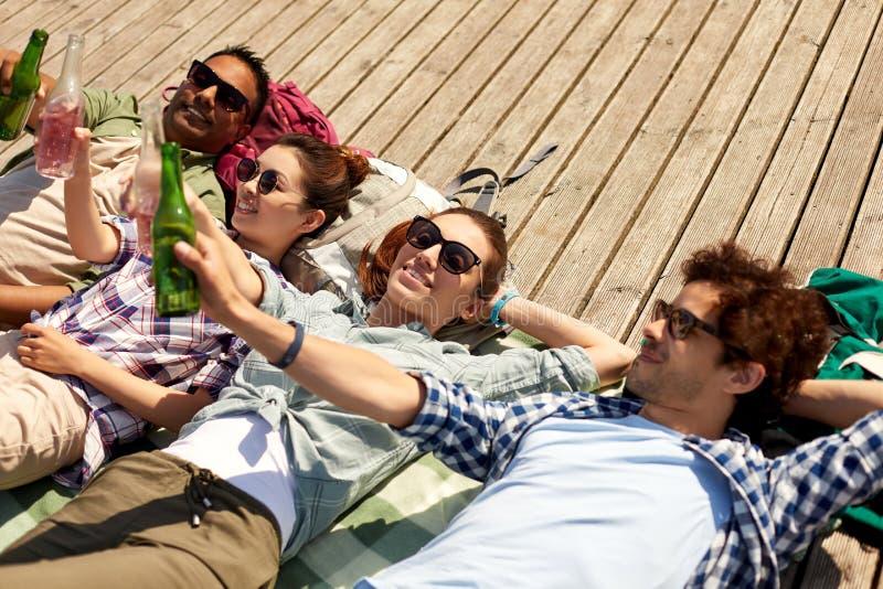 Freunde, die Bier und Apfelwein auf hölzerner Terrasse trinken stockfotos