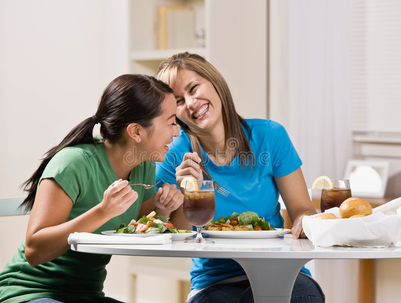 Freunde, die das gesunde Mittagessen und das Lachen essen lizenzfreie stockbilder