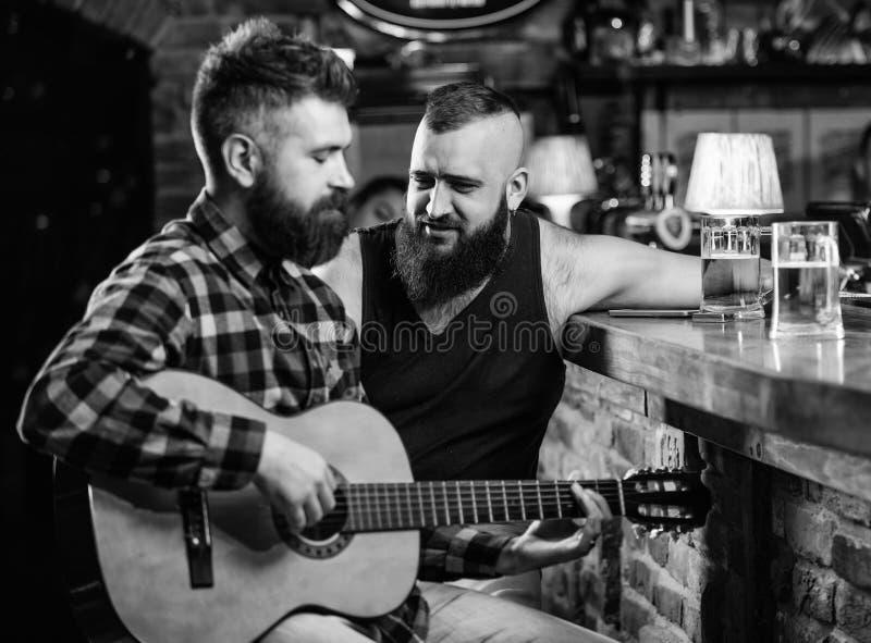 Freunde, die in der Bar oder in der Kneipe sich entspannen Wirkliche Mannfreizeit Grobe b?rtige des Hippies wenden Freizeit mit F stockfotografie