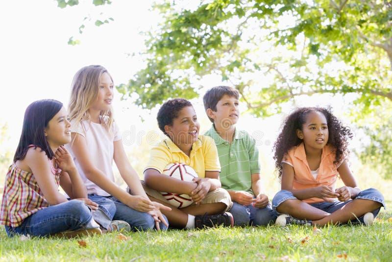 Freunde, die draußen mit Fußballkugel sitzen lizenzfreies stockbild