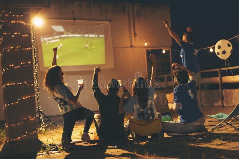 Freunde, die ein Fußballspiel aufpassen lizenzfreies stockfoto
