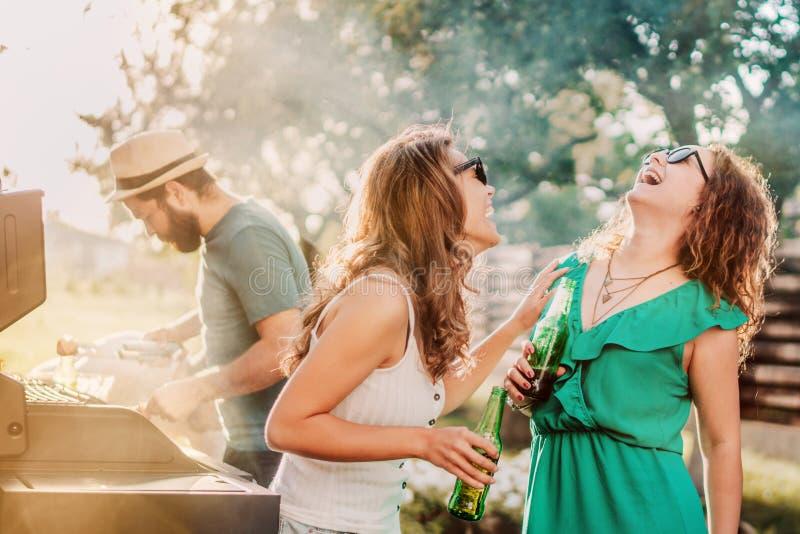 Freunde, die eine Grillpartei und -mädchen lachen und trinken helle Biere an einem Sommerabend haben lizenzfreie stockfotos