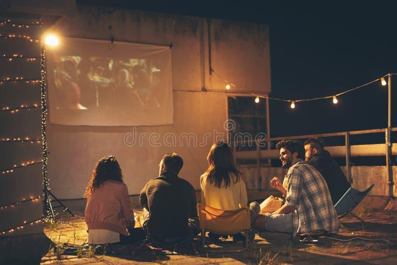 Freunde, die einen Film auf einer errichtenden Dachspitzenterrasse aufpassen lizenzfreie stockfotografie