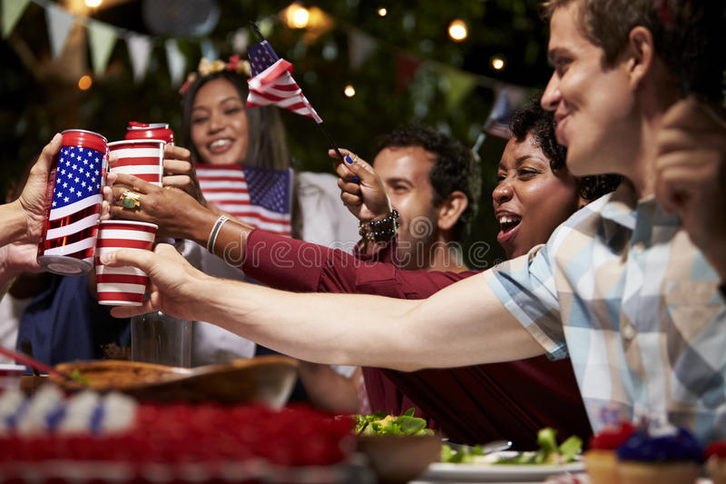 Freunde, die einen Toast 4. von Juli-Feiertag feiern lassen stockbilder