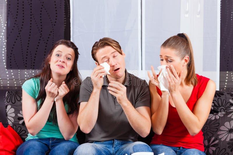 Freunde, die einen traurigen Film in Fernsehen aufpassen stockbilder