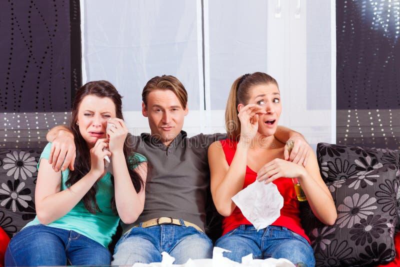 Freunde, die einen traurigen Film in Fernsehen aufpassen lizenzfreies stockfoto