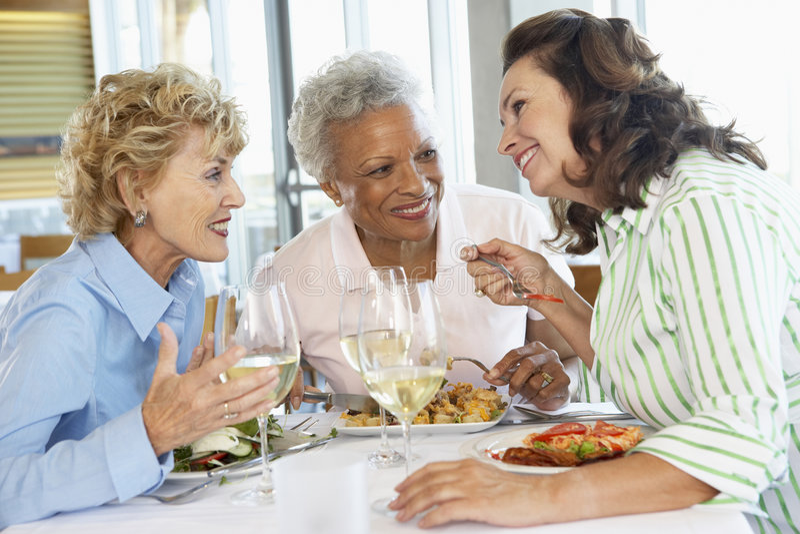 Freunde, die an einer Gaststätte zu Mittag essen stockfotos