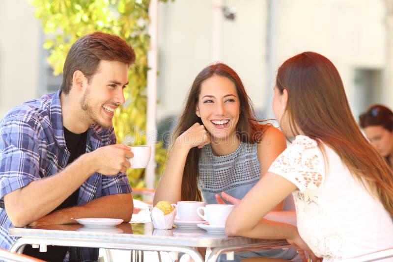 Freunde, die in einer Kaffeestubeterrasse sprechen stockbild