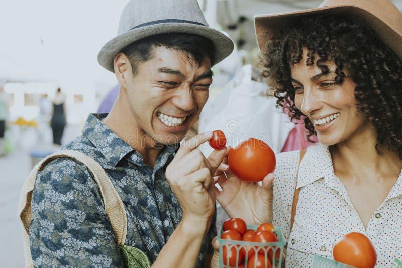 Freunde, die frische Tomaten an einem Landwirtmarkt kaufen lizenzfreies stockbild