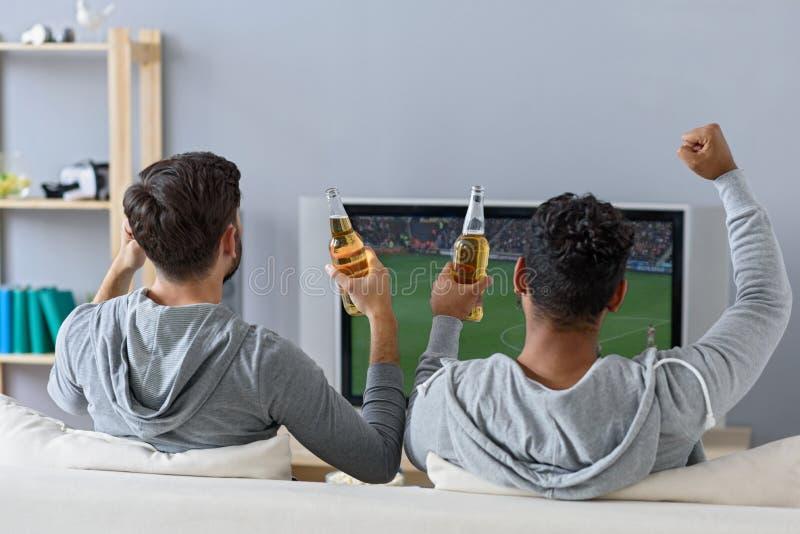 Freunde, die Fußball in Fernsehen genießen lizenzfreie stockfotos