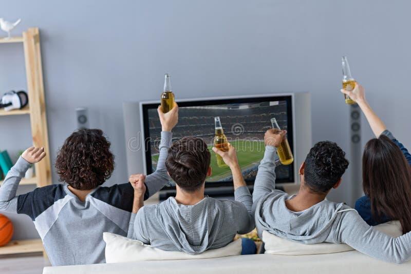 Freunde, die Fußball in Fernsehen genießen lizenzfreies stockfoto