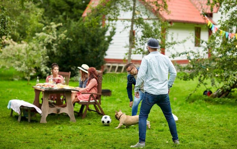Freunde, die Fußball mit Hund am Sommergarten spielen lizenzfreies stockfoto