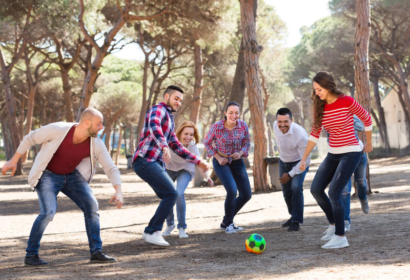 Freunde, die Fußball spielen lizenzfreie stockfotografie