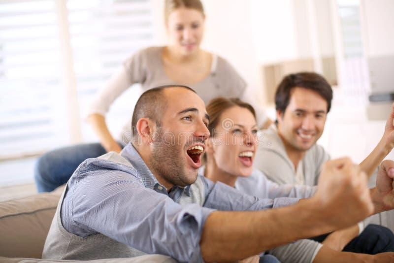 Freunde, die Fußballspiel aufpassen, aufgeregt zu sein stockbild