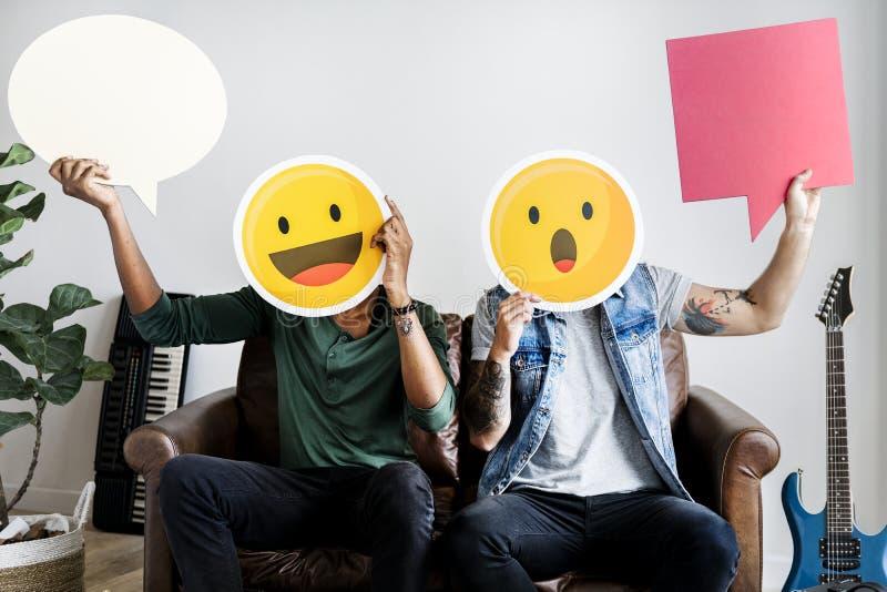 Freunde, die Gesichter eines ausdrucksvolle Emoticon und Spracheblasen halten lizenzfreie stockfotos
