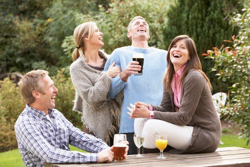 Freunde, die Getränk im Pub-Garten genießen lizenzfreies stockfoto