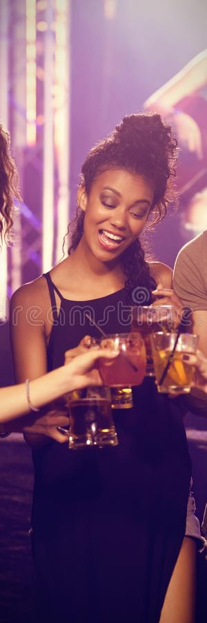 Freunde, die Getränke mit Ausführendem im Hintergrund rösten stockfotografie