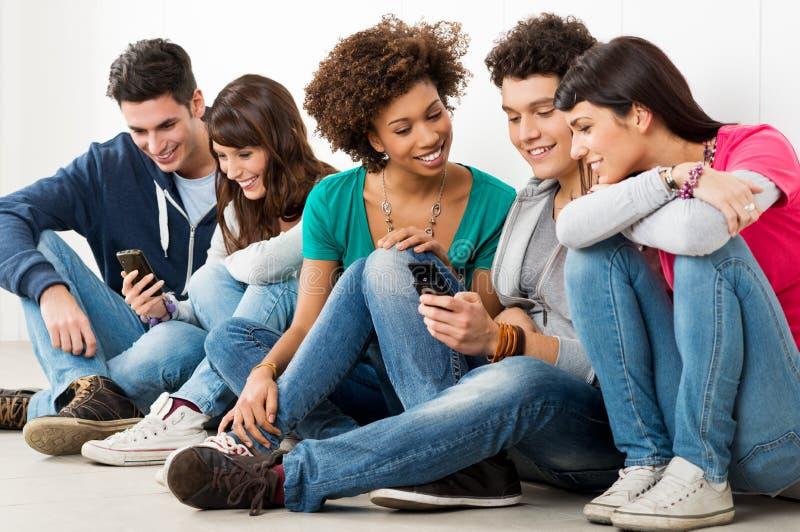 Freunde, die Handy betrachten lizenzfreies stockbild