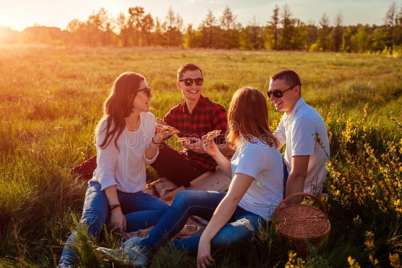Freunde, die heraus hängen und draußen Pizza essen Frauen und Männer, die Picknick bei Sonnenuntergang haben Kerle, die Spaß habe stockbild