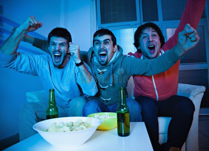 Freunde, die im Fernsehen Sport aufpassen lizenzfreies stockfoto