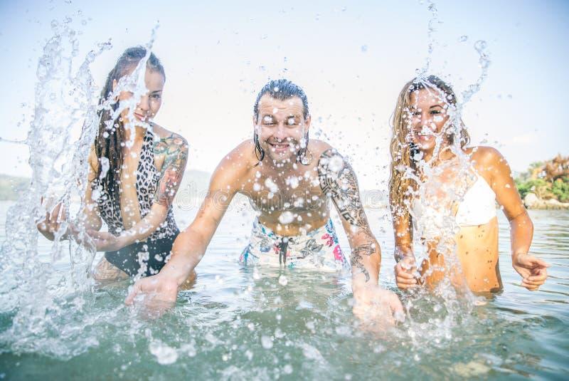 Freunde, die im Meer spielen lizenzfreies stockfoto