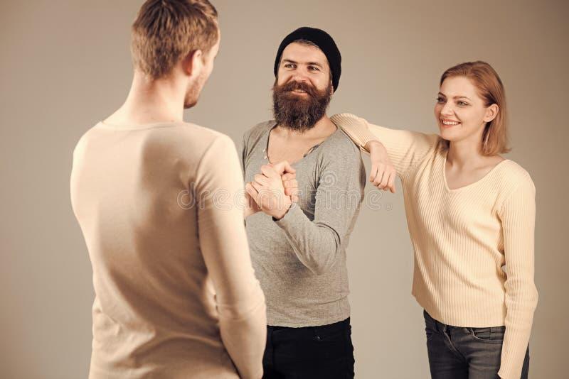 Freunde, die Konzept treffen Männer und Frau auf lächelnden Gesichtern auf grauem Hintergrund Männer, welche die Hände, froh, sic stockfoto