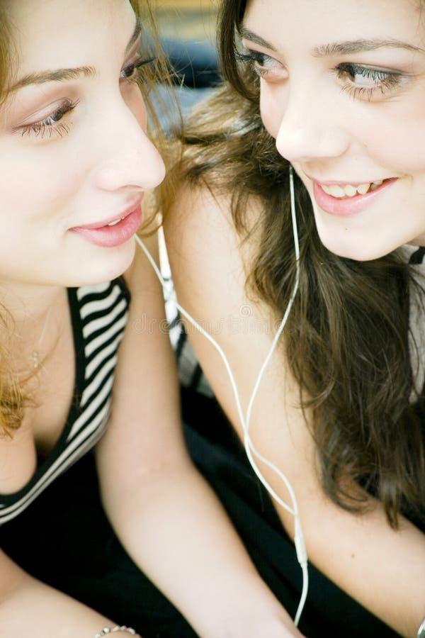 Freunde, die Kopfhörer teilen lizenzfreies stockfoto