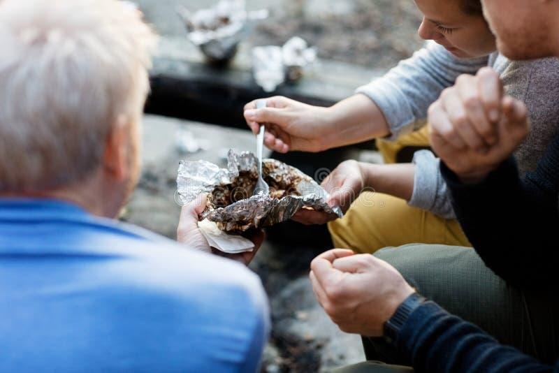 Freunde, die Lebensmittel in der Folie am Wald essen lizenzfreies stockbild