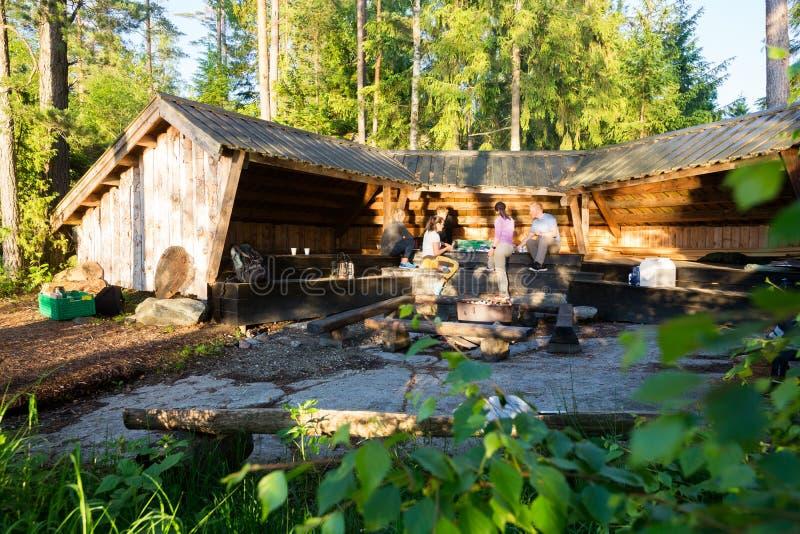 Freunde, die Lebensmittel durch Halle im Wald zubereiten lizenzfreies stockfoto