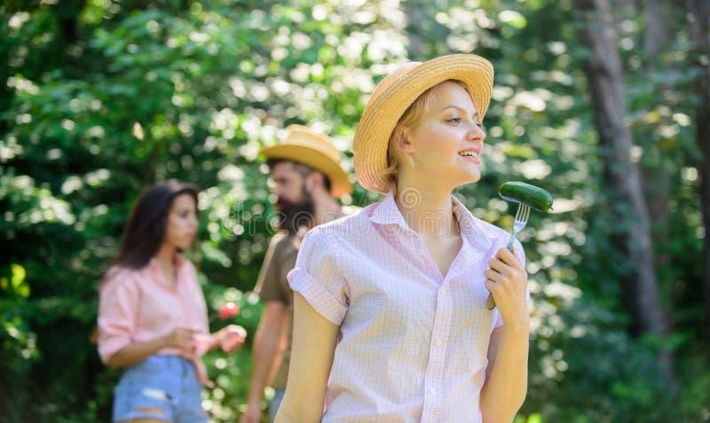 Freunde, die Lebensmittelpicknick essen Großer Appetit der Naturzustands-Ursache Damenvegetarier im Strohhut isst grünes organisc lizenzfreie stockbilder