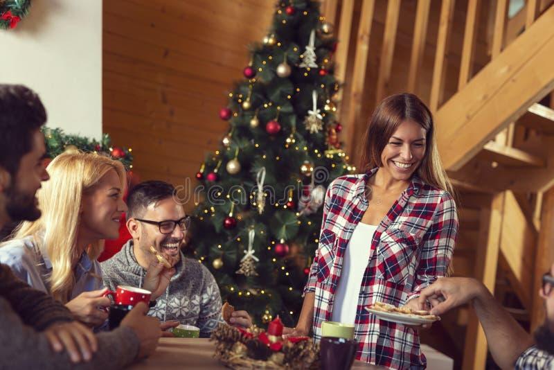 Freunde, die Lebkuchen Weihnachtsplätzchen essen lizenzfreie stockfotografie