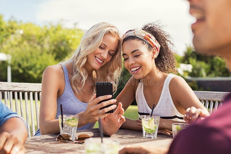Freunde, die mit Smartphone lächeln stockfotos