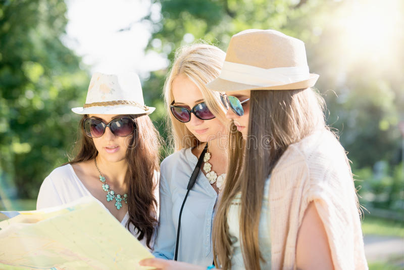 Freunde, die nach Richtungen auf eine Karte an den Sommerferien suchen lizenzfreie stockfotografie