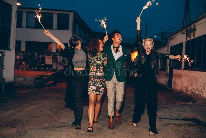Freunde, die Nacht mit Wunderkerzen genießen stockfotografie