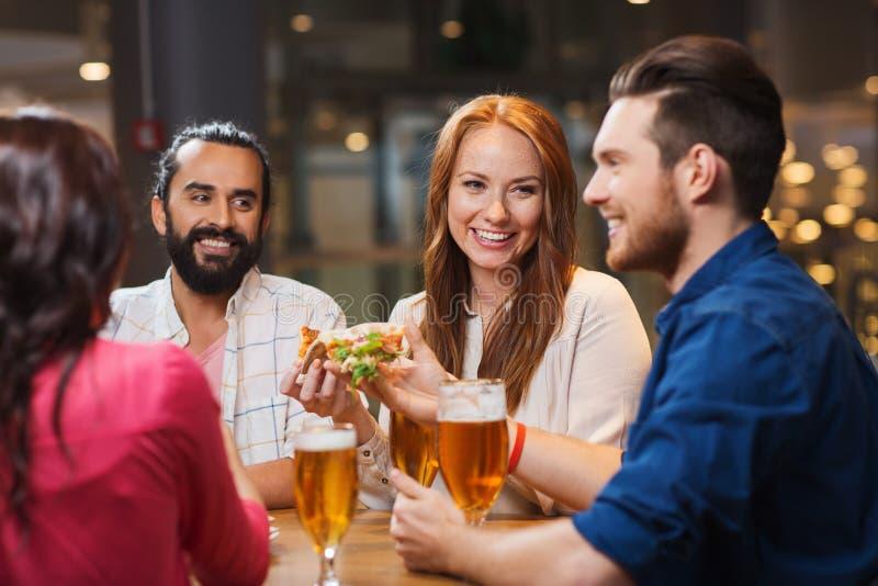 Freunde, die Pizza mit Bier am Restaurant essen stockbild