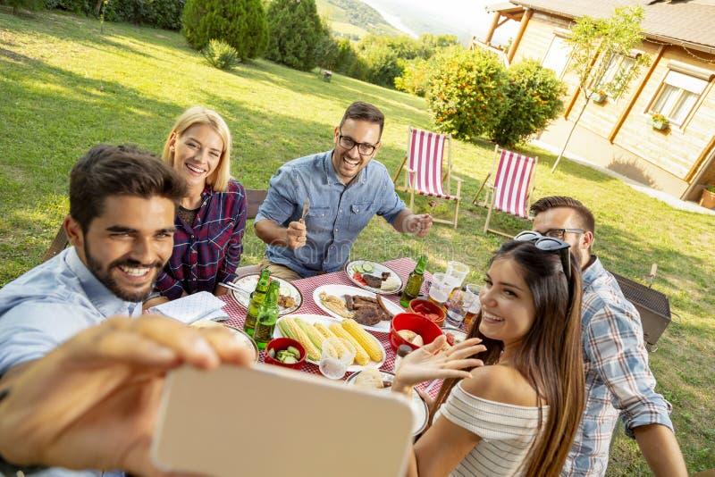 Freunde, die selfies an der Grillpartei nehmen stockbild