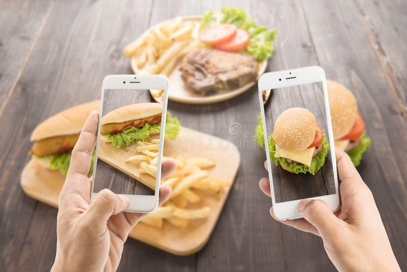 Freunde, die Smartphones verwenden, um Fotos des Hotdogs und des hamburge zu machen lizenzfreies stockfoto