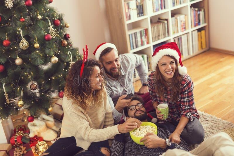 Freunde, die Spaß aufpassende Weihnachtsfilme haben stockfotos