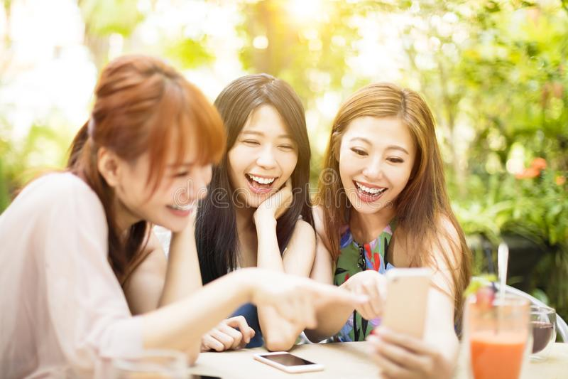 Freunde, die Spaß haben und intelligentes Telefon betrachten lizenzfreies stockbild