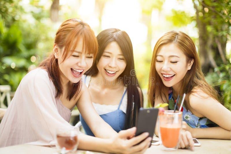Freunde, die Spaß haben und intelligentes Telefon betrachten stockbild