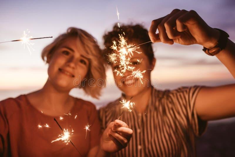 Freunde, die Spaß mit Wunderkerzen auf dem Strand bei Sonnenuntergang haben stockfotos