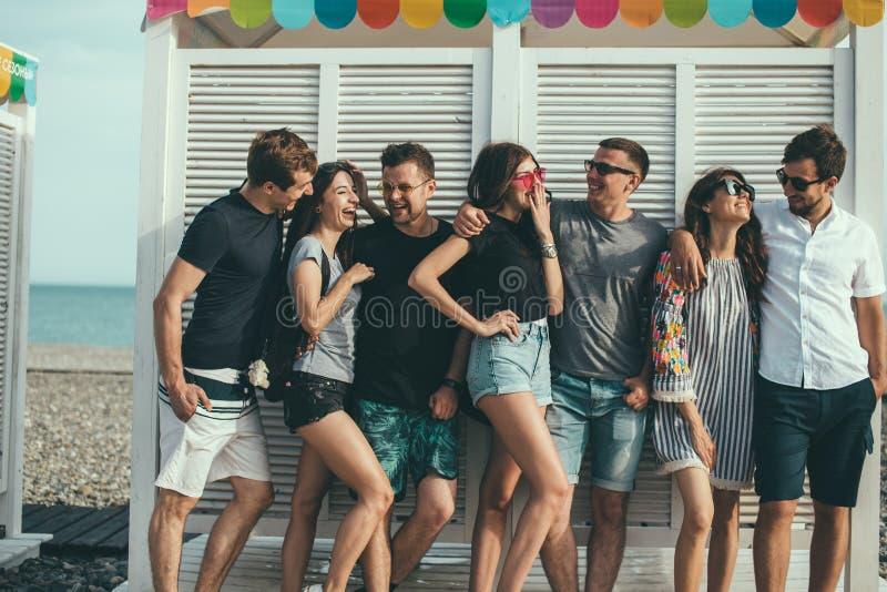 Freunde, die Spaß zusammen auf den Strand-Ferien, Kamera schauend haben stockfotos