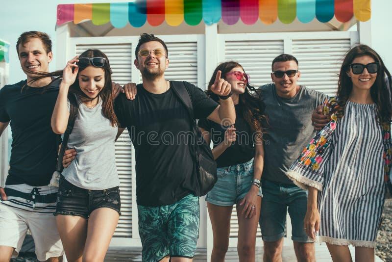 Freunde, die Spaß zusammen auf den Strand-Ferien, Kamera schauend haben lizenzfreie stockfotografie