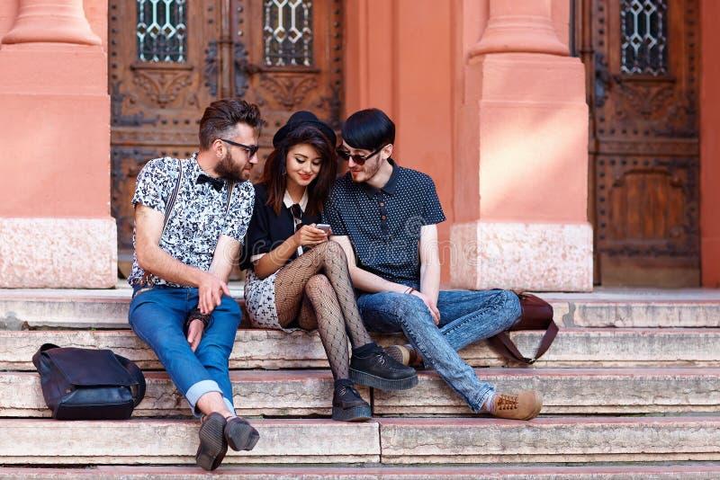 Freunde, die Spaß zusammen auf Treppe der Universität haben stockfotografie
