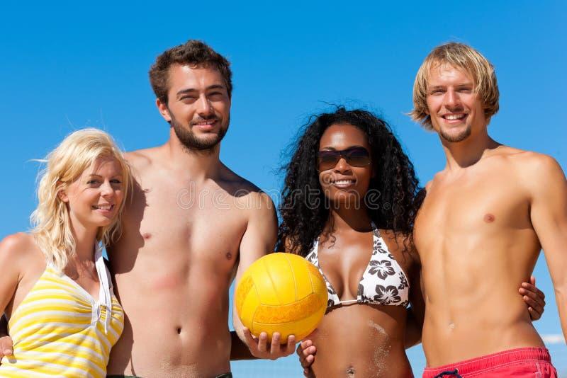 Freunde, die Strandvolleyball spielen lizenzfreie stockbilder
