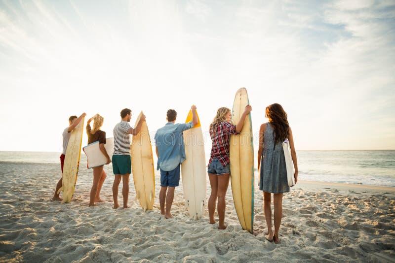 Freunde, die Surfbrett auf dem Strand halten stockfotos