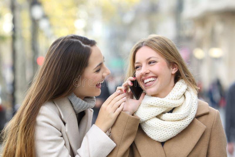 Freunde, die am Telefon auf der Straße im Winter sprechen lizenzfreies stockbild