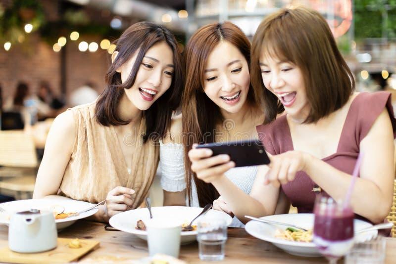 Freunde, die Telefon des Abendessens und des Aufpassens intelligentes im Restaurant haben lizenzfreie stockfotografie