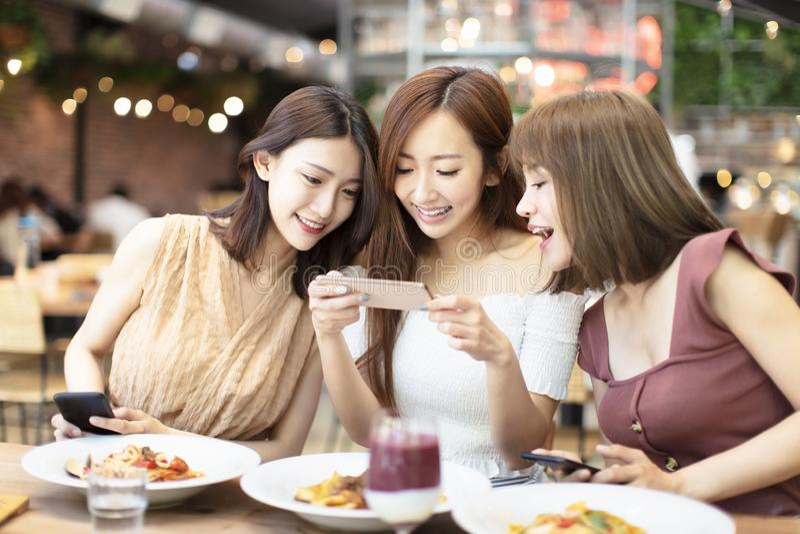 Freunde, die Telefon des Abendessens und des Aufpassens intelligentes im Restaurant haben stockfotos